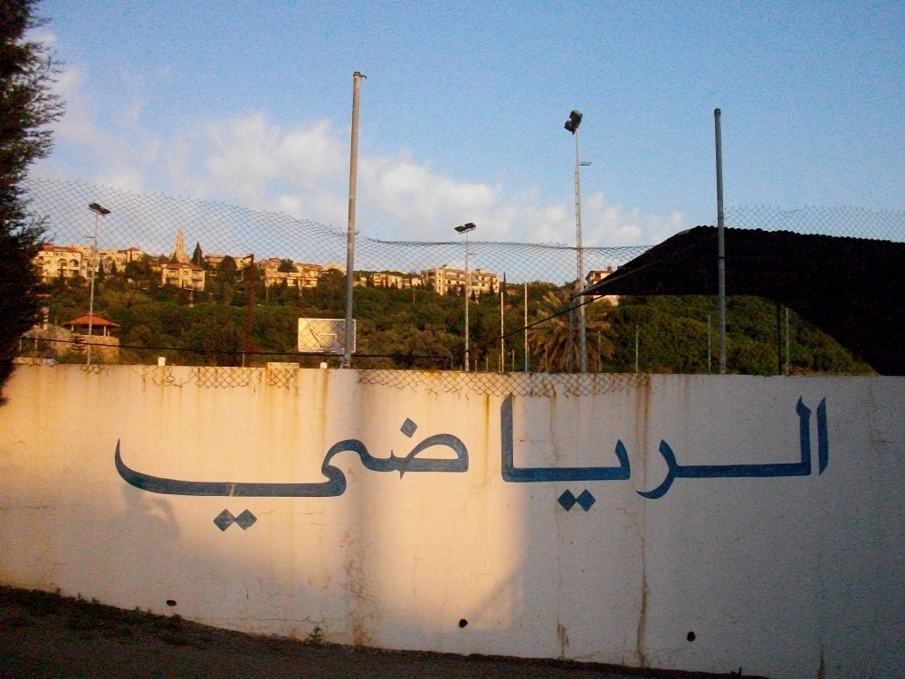 "sports field with ""al-riyadi"" lettering"