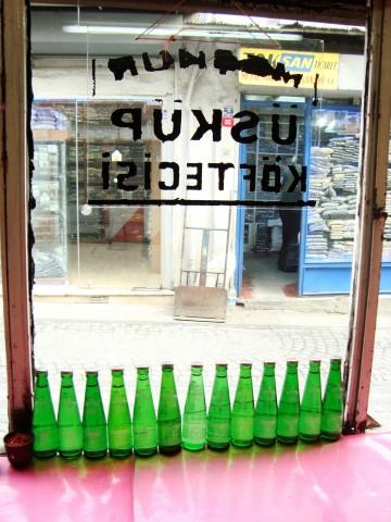 Köfte restaurant window with green glass bottles